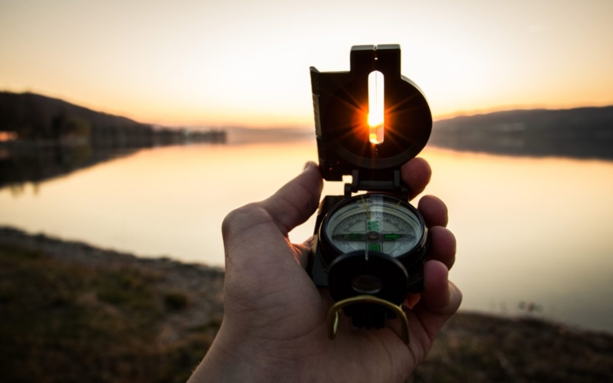 A hand holding a compass overlooking a lake in the sunset