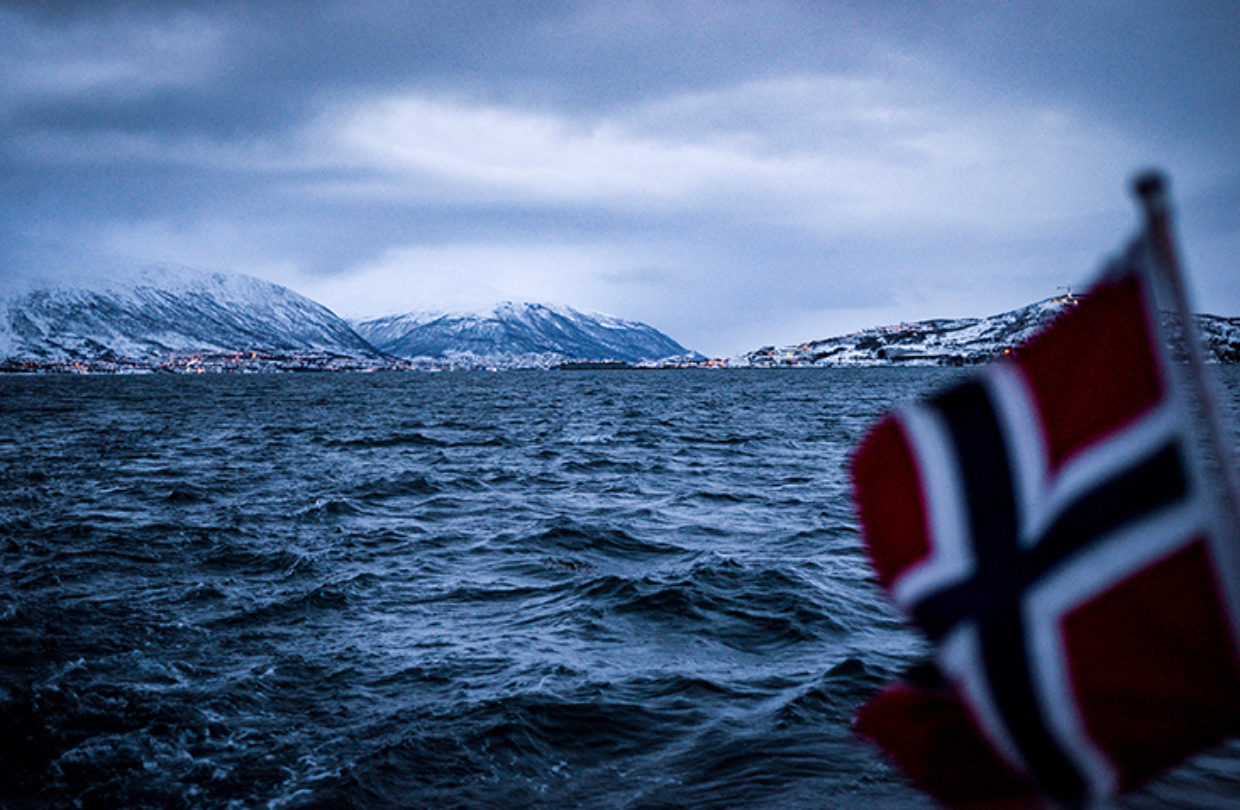 A photo with a Norwegian flag in the foreground, overlooking a fjord and mountains in the background.
