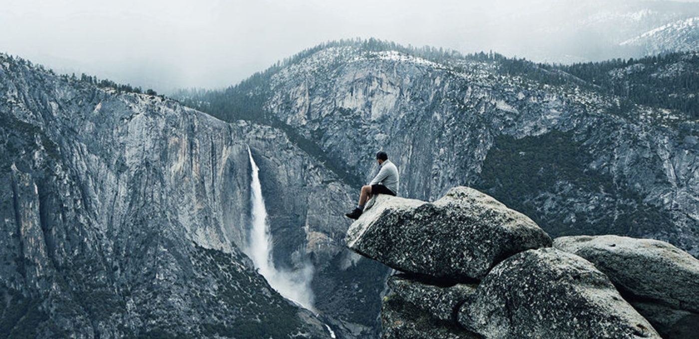 A person sitting on the edge of a rock looking out on a view of mountains