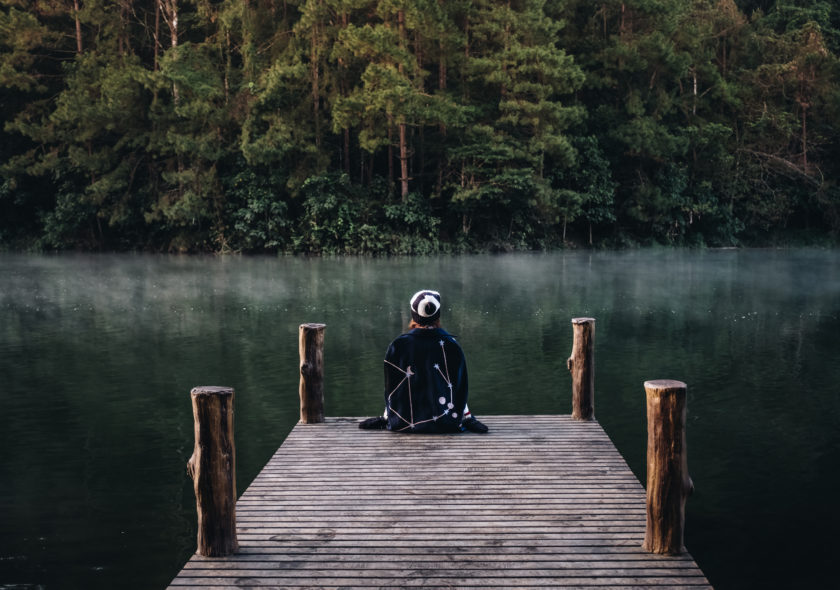 Woman sitting on dock looking out