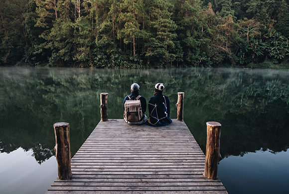 Two children sitting on a dock on a lake in the forest, looking out