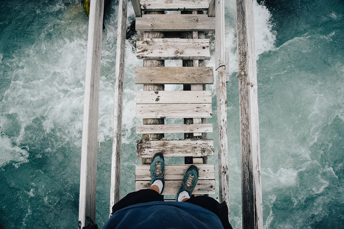 Feet with hiking boots seen from above, standing on a wooden bridge leading across water